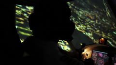 Pilot in headset maneuvering airplane above evening city, responsible job Stock Footage