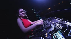 Dj girl in red dress spinning at turntable in nightclub. Headphones. Mixing - stock footage
