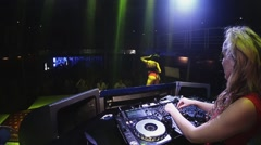 Dj girl in red dress spinning at turntable in nightclub. Headphones. Mc girl Stock Footage