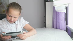 Cute little girl uses a digital tablet computer - stock footage