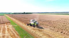 Flying next to combine harvesting destroyed crop 4K Stock Footage