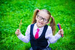 Portrait of adorable little school girl in glasses with pencils outdoor - stock photo