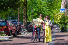 Young happy couple with city map on bikes in Amsterdam - stock photo