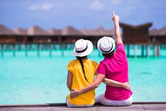 Young couple on beach jetty near water villa in honeymoon - stock photo