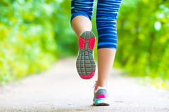 Close-up on shoe of athlete runner woman feet running on road Stock Photos