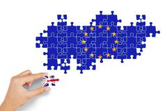 Hand plays puzzle with flag of England and EU - stock photo