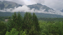 AERIAL: Flying above the lush forest in big mountain valley Stock Footage
