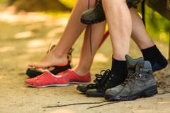 Girl and boy compare footwear. Stock Photos