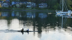 2 man and 8 man scull boats passing in Eagle Harbor early morning light Stock Footage
