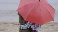 4K Smiling young romantic couple with red umbrella spending time on the beach Stock Footage