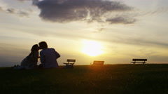 4K Wide shot of silhouette couple sharing a sunset kiss, in slow motion - stock footage
