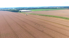Flyover field with harverster picking wheat 4K Stock Footage
