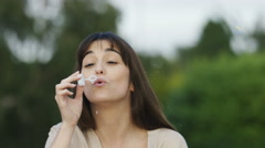4K Attractive woman laughs after blowing bubbles, in slow motion - stock footage