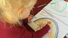 Young girl colouring a picture indoors Stock Footage