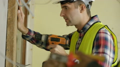 4K Construction workers on a building site drilling & checking wiring Stock Footage