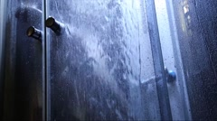 Showering woman silhouette blurred by the transparent door. woman taking shower Stock Footage