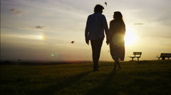 4K Silhouette couple walk towards the sunset holding hands, in slow motion - stock footage