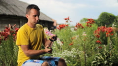 Young man use tablet for game near flowers in garden. White, red and purple Stock Footage