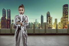 Woman wearing latex jumpsuit posing on building rooftop Stock Photos