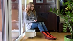 Cute woman have fun with laptop sitting on warm radiator at home Stock Footage