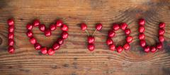 Ripe organic homegrown cherries on wooden background, I love you text Stock Photos