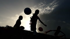 Group of kids passing under the sun with baloons - Slow Motion Stock Footage