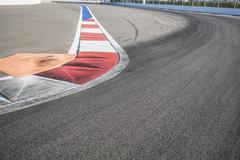 Texture of motor race asphalt and red white curb. Close up on Grand Prix street Stock Photos