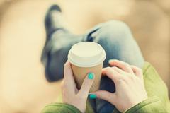 Autumn concept, anonymous woman enjoying takeaway coffee cup on sunny cols fa - stock photo