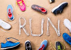 Running shoes and run sign made of shoelaces, sand Kuvituskuvat