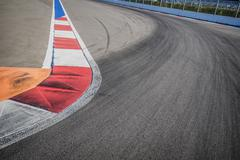Texture of motor race asphalt and red white curb. Close up on Grand Prix street - stock photo