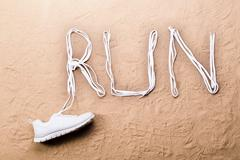 Running shoe and run sign made of shoelaces, sand Kuvituskuvat