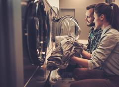 Young cheerful couple doing laundry together at laundromat shop Kuvituskuvat