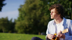 4K Attractive young man playing a ukulele, in slow motion Stock Footage