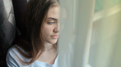 Side view portrait of a girl looking away through a window at home. RAW video Stock Footage