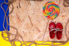 Small red boat shoes near big multi-colored lollipop  and rope on wooden desk - stock photo