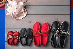 Family boat shoes on wooden background. Four pair of red and black boat shoes - stock photo