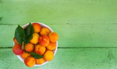 Bowl with apricots on a wooden background Stock Photos