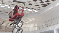 Electricians install ceiling lights using scissor lift in large building Stock Footage