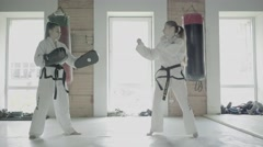 Slowmotion Two Taekwondo Girls Train For A Kick On Boxing Paw Stock Footage