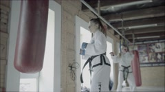 Two Taekwondo Girls Train For A Kick Into Punching Bag Stock Footage