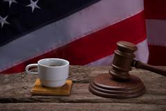 Gavel and white cup. Stock Photos