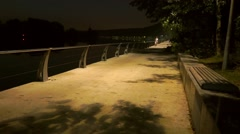 Two cyclists passing by on park embankment at late evening. Slow motion shot Stock Footage