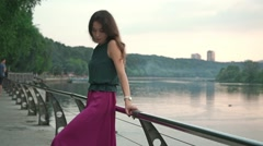 Romantic brunette girl standing on park embankment at evening. Slow motion shot Stock Footage