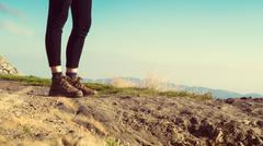 Unrecognizable female hiker on top of the mountain wearing hiking boots Stock Photos