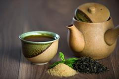Ceramic teapot, cup of black tea with mint leaves and brown sugar Stock Photos