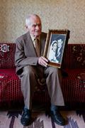 Senior man holding his wedding photograph. Love forever concept - stock photo