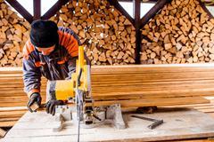 Carpenter working. Man cutting plank by circular saw - stock photo