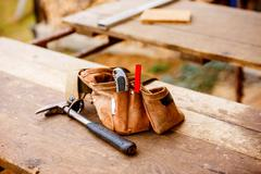 Carpenters bag with belt full of tools, wooden table - stock photo