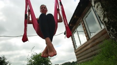 Anti-gravity Yoga, woman doing yoga exercises in the park Stock Footage