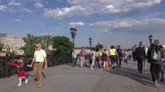 Families, couples and teenagers walk on pedestrian footbridge at Moscow centre Stock Footage